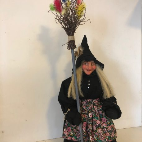 Kitchen witch standing with broom